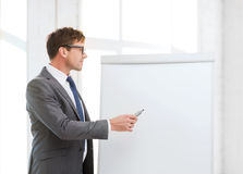 Businessman pointing to flip board in office Stock Images