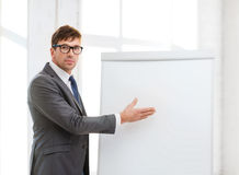 Businessman pointing to flip board in office Stock Photo
