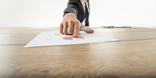 Businessman pointing to a graph on a desk Stock Photography