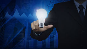Businessman pointing to light bulb over graph and city tower, Id Royalty Free Stock Photo