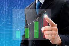 Businessman pointing to the peak. Businessman in dark gray suit pointing to the highest point of the bar chart royalty free stock image