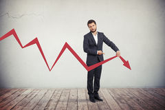 Businessman pointing to red graph arrow down. Stock Photos
