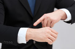 Businessman pointing to something at his hand. Time, business and new technology concept - close up of businessman pointing to something at his hand Stock Photo