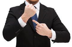 Businessman pointing to something at his hand. Time, business and new technology concept - close up of businessman pointing to something at his hand Royalty Free Stock Photos