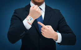 Businessman pointing to something at his hand Royalty Free Stock Image