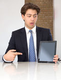 Businessman pointing to a tablet in horror Stock Photography
