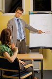 Businessman pointing to whiteboard and explaining to woman Stock Images