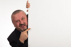 Businessman pointing to whiteboard he is hiding behind Stock Photography
