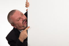 Businessman pointing to whiteboard he is hiding behind Royalty Free Stock Photo