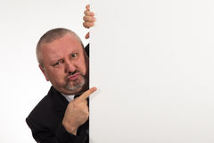 Businessman pointing to whiteboard he is hiding behind Royalty Free Stock Image