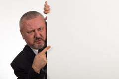 Businessman pointing to whiteboard he is hiding behind Royalty Free Stock Images