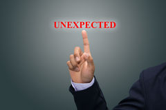 Businessman pointing to the word Unexpected Royalty Free Stock Photo