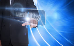 Businessman pointing to word usability. Against background with bright lines Royalty Free Stock Photography