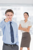 Businessman pointing towards camera with woman in office Royalty Free Stock Photos