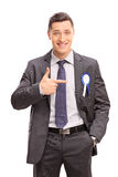 Businessman pointing towards a ribbon on his coat Royalty Free Stock Images
