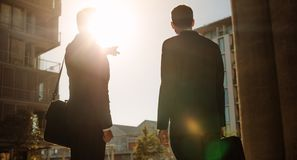 Businessman pointing towards something to colleague standing on Royalty Free Stock Photography