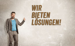 Businessman pointing up towards text, We offer solutions. In German studio portrait on grunge wall Stock Image