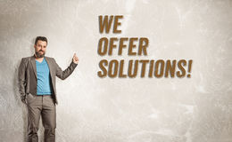 Businessman pointing up towards text, We offer solutions Stock Photography