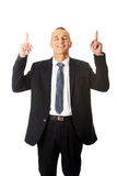 Businessman pointing upwards and smiling at camera Stock Photo