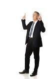 Businessman pointing upwards Stock Photo