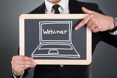 Businessman pointing webinar sign drawn on slate stock image