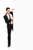 Businessman pointing at white banner. Young man in black suit pointing at the banner. Full length studio shot isolated on white Stock Photos