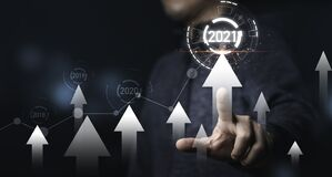 Businessman pointing with white up increasing arrow with virtual infographic 2021 for business growth concept