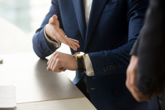 Businessman pointing on wristwatch, punctuality, time management. Close up view of businessman wearing suit pointing on hand expensive luxury wristwatch at stock photography