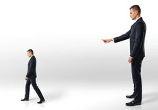 Businessman points at another man following in the direction indicated. Stock Photos
