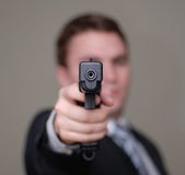 Businessman Points Gun with Shallow Depth of Field. Young businessman pointing a gun towards the camera. Shallow depth of field royalty free stock image