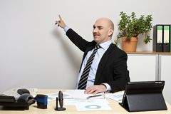 Businessman points to a presentation on the wall. Stock Image
