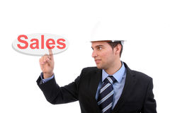 Businessman points to sales. Businessman in suit and hard hat pointing to sales written in red text on a white sign board with a white background Royalty Free Stock Photo