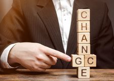 Businessman points to wooden blocks with the word Change to Chance. Personal development. Career growth or change yourself concept royalty free stock image