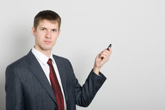 Businessman points toward your mobile phone Royalty Free Stock Photo