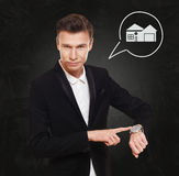 Businessman points at watch, real estate concept Stock Photo