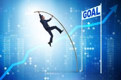 The businessman pole vaulting towards his goal in business concept Stock Image