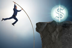 The businessman pole vaulting towards his money goal Royalty Free Stock Photography