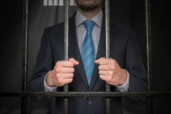 Businessman or politician behind bars in prison cell stock photography