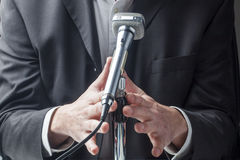 Businessman or politician speaking up on microphone Stock Photo
