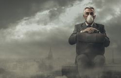 Businessman and polluted city. Businessman sitting on a rooftop in a polluted city, he is pensive and looking away: business and pollution concept royalty free stock image