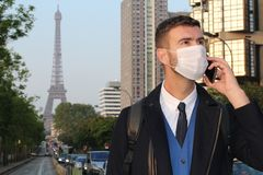 Businessman with pollution mask calling by phone in Paris.  royalty free stock photography