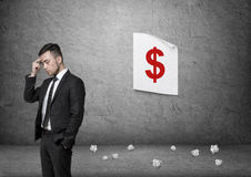 Businessman pondering with dollar sign poster on background Stock Images