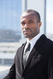 Businessman portrait on skyscrapers background. Black businessman portrait on skyscrapers background Royalty Free Stock Image