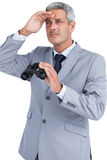 Businessman posing with binoculars and looking away Stock Photos