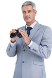 Businessman posing with binoculars Stock Images