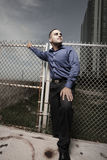 Businessman posing by a fence Stock Images