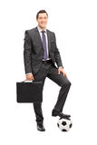 Businessman posing with a football Royalty Free Stock Image