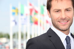 Businessman posing in front flags Stock Photo