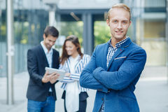 Businessman posing in front of a small group of business p Royalty Free Stock Image