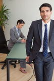 A businessman posing with his colleague. Portrait of a businessman posing while his colleague is working in an office Stock Photos